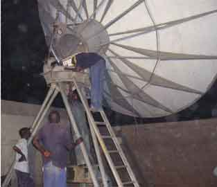 Working at night during rain repointing a customer's large 6.8m satellite dish in Nigeria