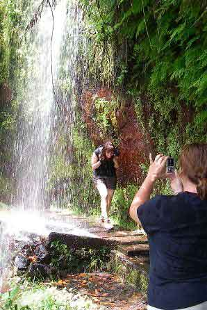 Walking under waterfall along levada path