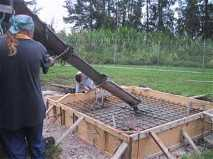 Pouring concrete to form the antenna base. Note the wooden shuttering and reinforcing iron grid.  The three foot fittings for the dish legs are already accurately positioned.